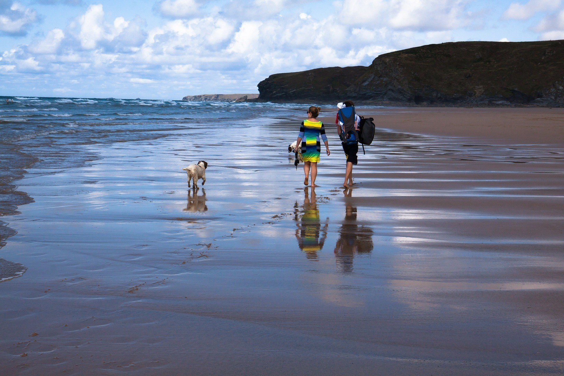 family on beach with backpack